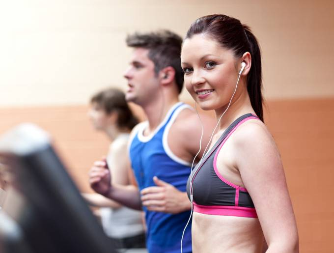 Young beautiful athletes with earphones exercising on a running machine