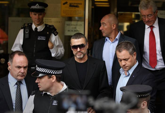 LONDON, ENGLAND - AUGUST 24:  Singer George Michael (C) leaves  Highbury Corner Magistrates Court surrounded by press and police on August 24, 2010 in London, England. Mr Michael pleaded guilty to driving under the influence of drugs and possessing cannabis after he crashed his car into a photo processing shop in London on July 4, 2010.  (Photo by Peter Macdiarmid/Getty Images)