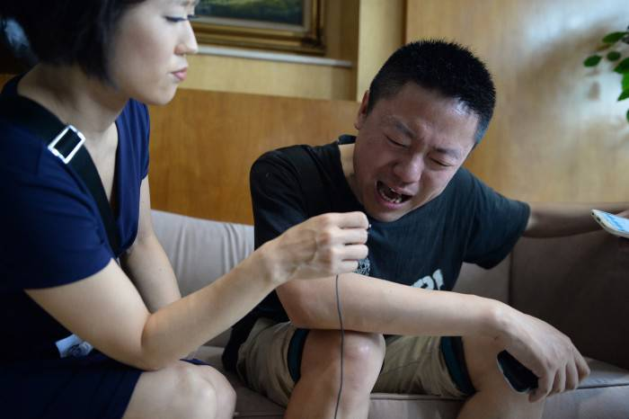 A relatives (R) of missing passengers who were on a ship which sank in the powerful Yangtze river the night before cries as he accepts an interview from a journalist outside a travel agency in Shanghai on June 2, 2015. China mounted a rescue operation on June 2 after the ship which was reportedly carrying more than 450 people sank in the powerful Yangtze river after being hit by stormy weather.   CHINA OUT     AFP PHOTO        (Photo credit should read STR/AFP/Getty Images)