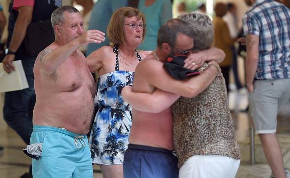 Tourists console each other following a shooting attack in the resort town of Sousse, a popular tourist destination 140 kilometres (90 miles) south of the Tunisian capital, on June 26, 2015. At least 27 people, including foreigners, were killed in a mass shooting at a Tunisian beach resort packed with holidaymakers, in the North African country's worst attack in recent history. AFP PHOTO / FETHI BELAID        (Photo credit should read FETHI BELAID/AFP/Getty Images)