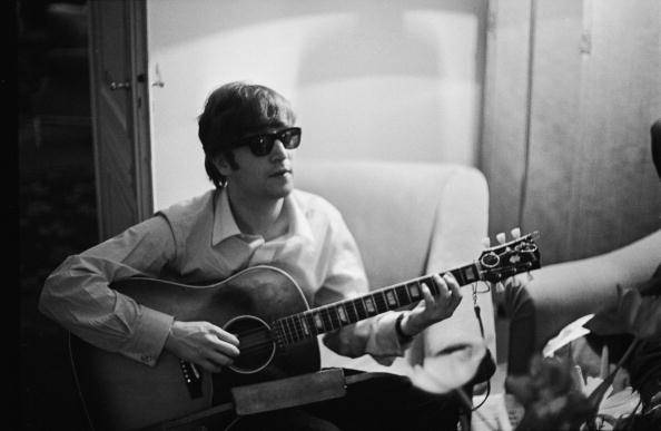 John Lennon (1940 - 1980) of the Beatles plays the guitar in a hotel room in Paris, 16th January 1964. (Photo by Harry Benson/Express/Hulton Archive/Getty Images)