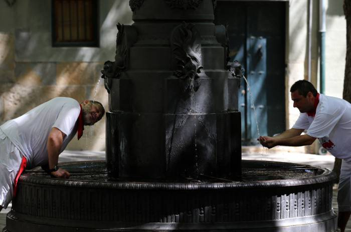 Two men cool off with water from a fountain of Pamplona during a hot summer day at the San Fermin Festival on July 7, 2015. The festival is a symbol of Spanish culture that attracts thousands of tourists to watch the bull runs despite heavy condemnation from animal rights groups.   AFP PHOTO/ CESAR MANSO        (Photo credit should read CESAR MANSO/AFP/Getty Images)