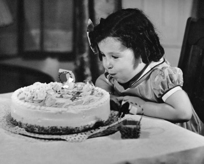 UNITED STATES - CIRCA 1950s:  Young girl blowing out candles on cake.  (Photo by George Marks/Retrofile/Getty Images)