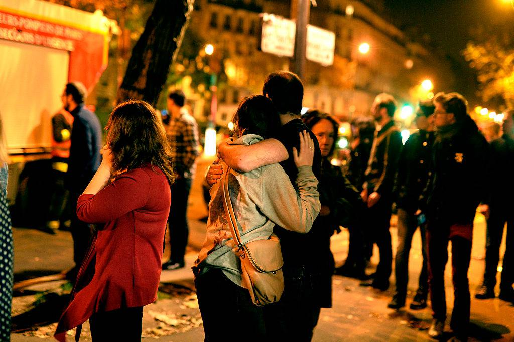 PARIS, FRANCE - NOVEMBER 13:  Parisians look at the scene outside the Bataclan concert hall after an attack on November 13, 2015 in Paris, France. According to reports, over 120 people were killed in a series of bombings and shootings across Paris, including at a soccer game at the Stade de France and a concert at the Bataclan theater. (Photo by Pascal Le Segretain/Getty Images)