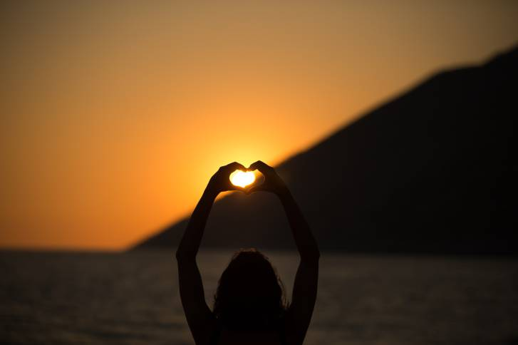 Vacation vitality healthy living concept.Silhouette hand in heart shape