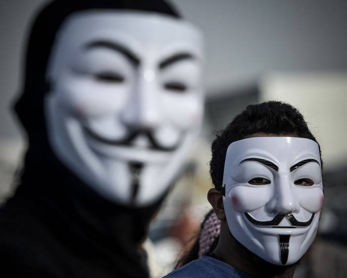 "Bahraini protesters wearing Guy Fawkes masks used by the Anonymous movement take part in a demonstration against the government and in solidarity with jailed freelance photographer Ahmed Humaidan in the village of Karranah, west of Manama, on March 1, 2013. Humaidan was arrested during a rally on December 29, 2012 and was charged with ""demonstrating illegally"" and ""using violence to assault police and damage public properties"". AFP PHOTO/MOHAMMED AL-SHAIKH        (Photo credit should read MOHAMMED AL-SHAIKH/AFP/Getty Images)"