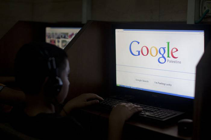 "A Palestinian boy opens the Palestinian homepage of Google's search engine reading ""Palestine"" at an internet cafe in east Jerusalem on May 3, 2013. Internet giant Google has recognised the Palestinians' upgraded UN status, placing the name ""Palestine"" on its search engine instead of ""Palestinian Territories,"" the US company said, raising the ire of Israel. AFP PHOTO/AHMAD GHARABLI        (Photo credit should read AHMAD GHARABLI/AFP/Getty Images)"