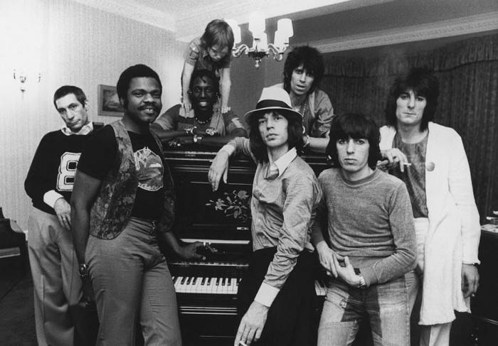 The Rolling Stones together in their hotel at 2 a.m. after a British concert, 19th May 1976. Accompanying the group on tour is Keith Richards' six year-old son Marlon. Left to right: Charlie Watts, keyboard player Billy Preston, percussionist Ollie Brown with Marlon Richards, Mick Jagger, Keith Richards, Bill Wyman and Ron Wood. (Photo by Daily Express/Hulton Archive/Getty Images)