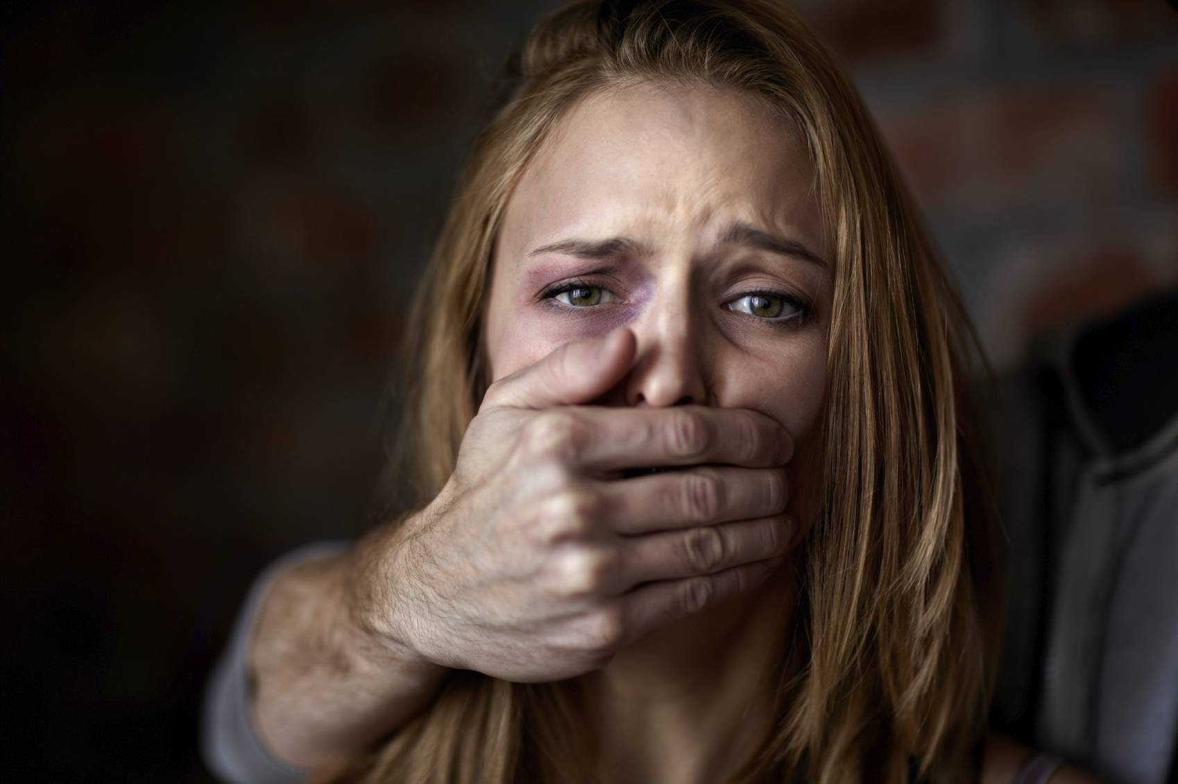 Abused young woman being silenced by her abuser