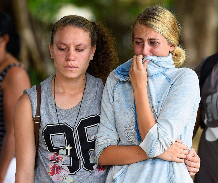 CAIRNS, AUSTRALIA - DECEMBER 20:  A Member of the public weeps at the scene of a memorial which is located in the park next the home of a multiple stabbing in the suburb of Manoora on December 20, 2014 in Cairns, Australia. Eight children have been found dead and a 37-year-old woman is in hospital with chest injuries at a home in North Queensland. The children, aged 18 months to 14 years have reportedly been stabbed and the women has been arrested for murder.  (Photo by Ian Hitchcock/Getty Images)