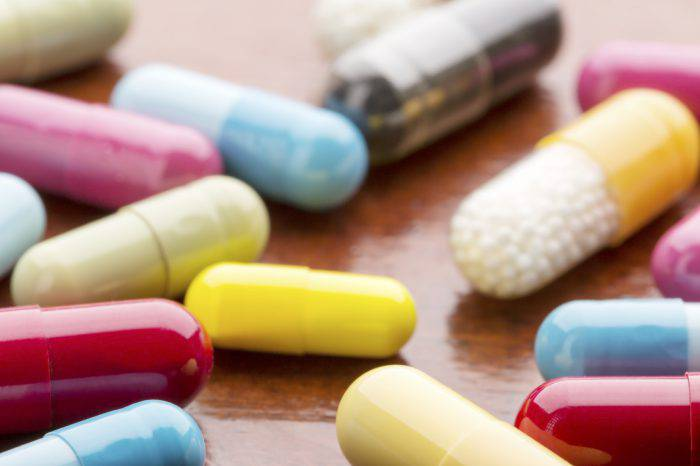 Various colorful medicine capsules on wooden table background