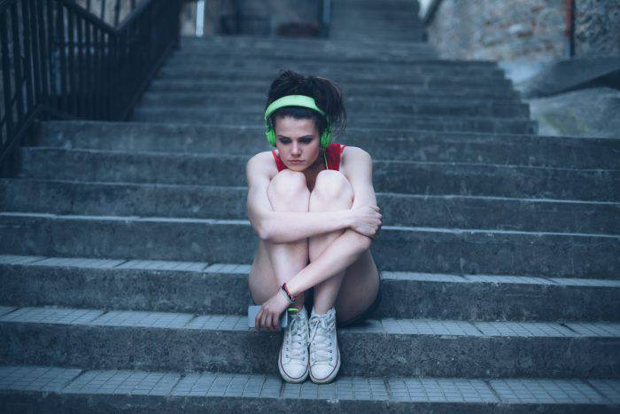 Sad girl with headphones sitting on stairs, arms around legs. Stairs, fence and stone walls on background.