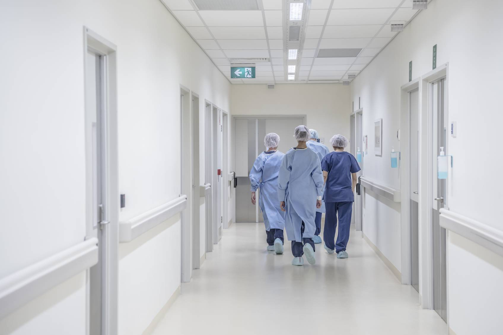 View from behind of four doctors in hospital corridor walking away from camera. Medical team in modern hospital corridor wearing surgical scrubs