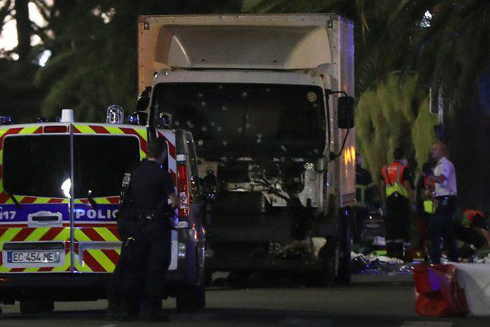 Police officers stand near a truck, with its windscreen riddled with bullets, that ploughed into a crowd leaving a fireworks display in the French Riviera town of Nice on July 14, 2016. At least 60 people were killed when a truck ploughed into a crowd watching a Bastille Day fireworks display in the southern French resort of Nice, prosecutors said early on July 15. Nice prosecutor Jean-Michel Pretre said the truck drove two kilometres (1.3 miles) through a large crowd that was watching the fireworks.  / AFP / VALERY HACHE        (Photo credit should read VALERY HACHE/AFP/Getty Images)