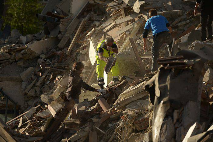 Resucers and residents clear debris in search for victims in damaged homes after a strong heathquake hit Amatrice on August 24, 2016. Central Italy was struck by a powerful, 6.2-magnitude earthquake in the early hours, which has killed at least three people and devastated dozens of mountain villages. Numerous buildings had collapsed in communities close to the epicenter of the quake near the town of Norcia in the region of Umbria, witnesses told Italian media, with an increase in the death toll highly likely. / AFP / FILIPPO MONTEFORTE        (Photo credit should read FILIPPO MONTEFORTE/AFP/Getty Images)