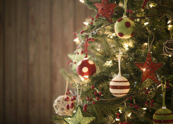 Christmas Eco friendly holiday tree with baubles and natural ornaments against a rustic, vintage, old wood background.